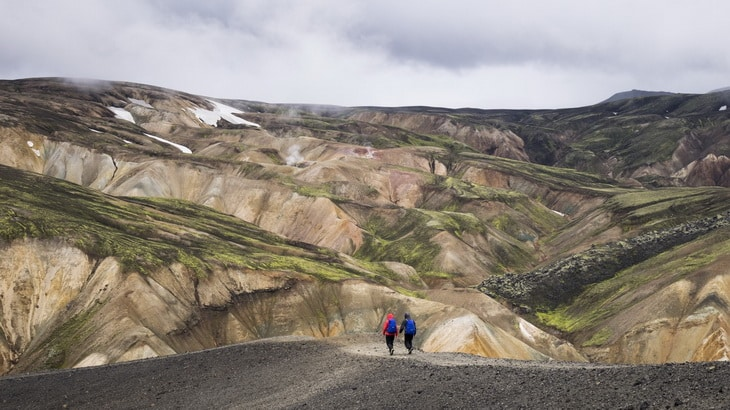 2 People Walking Towards the Mountain during Daytime