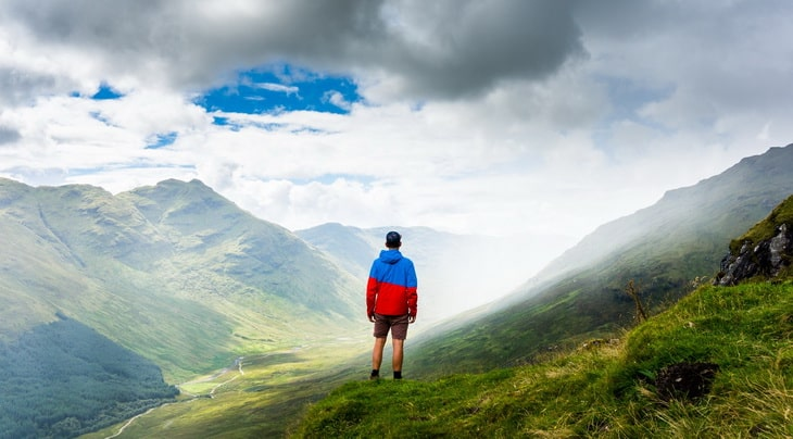 man watching the clouds on top of the mountains
