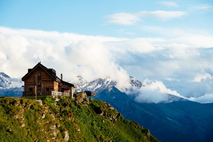 Photography of Brown Wooden House Top of Mountain Under White Sky during Daytime