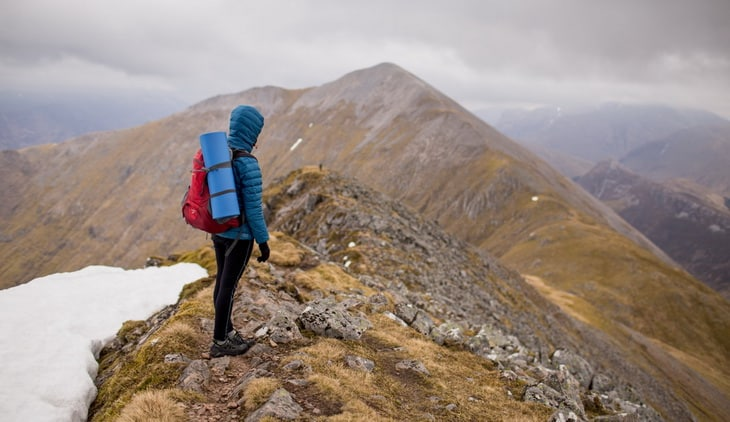 Person in Blue Hoodie Jacket Wearing Red Hiking Backpack Standing at the Top of Mountain Under White Sky during Daytime