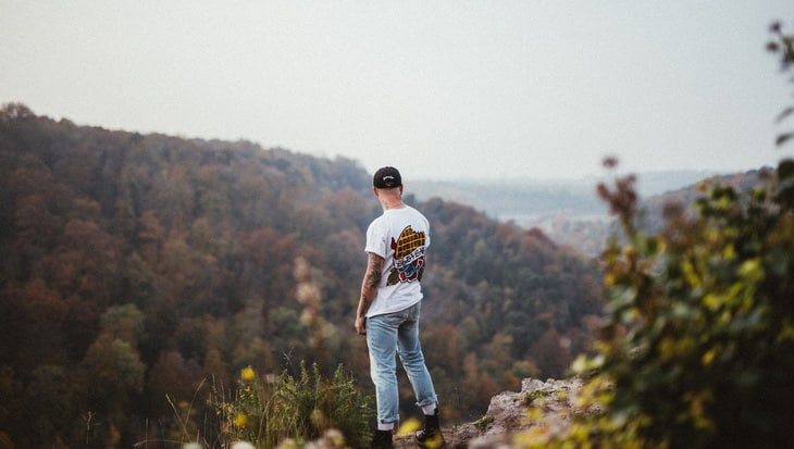Man in White Printed Crew Neck Shirt Standing on Isle of Mountain