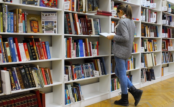 Woman Reading Book in a Bookstore
