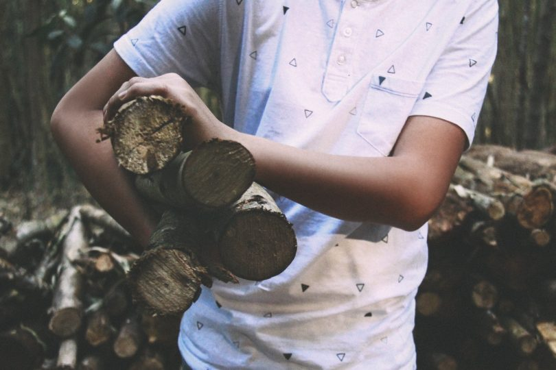 Man in White Polo Shirt Carrying on His Right Firewood Sticks