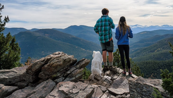 Young couple hiking with their dog