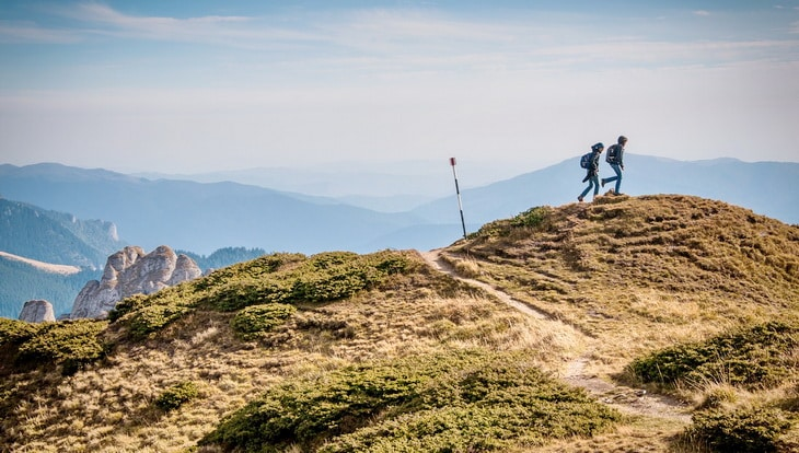 2 Person Hiking on Top of a Hill during Daytime