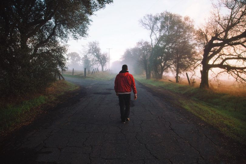 Man Wearing Red Hooded Jacket Standing on Road