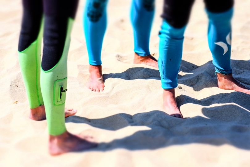 3 People Standing on Brown Beach