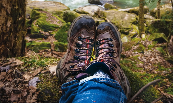 Close-up photo of a pair of boots in a man's legs