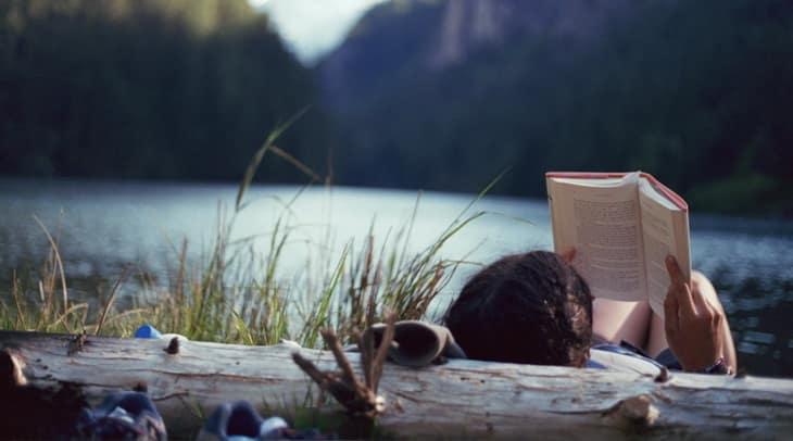 woman reading by lake