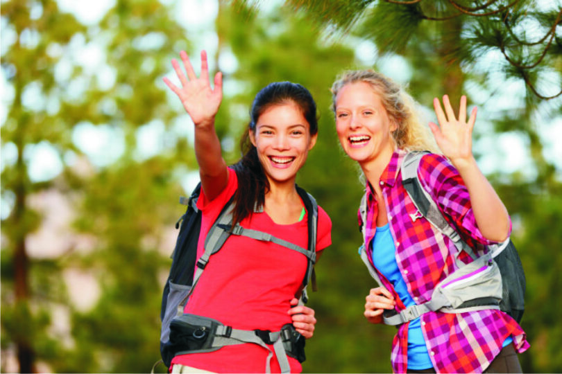 women say hello to other hikers