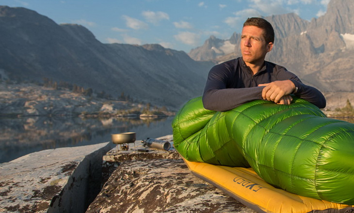 Man in a sleeping bag looking at the landscape