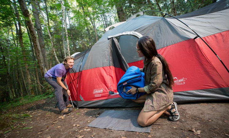 Two adults setting up the tent
