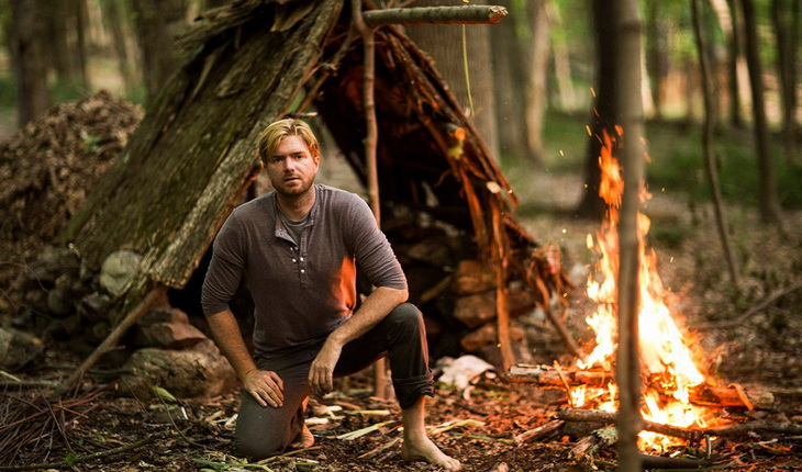 A man in the wild near a fire looking at the camera