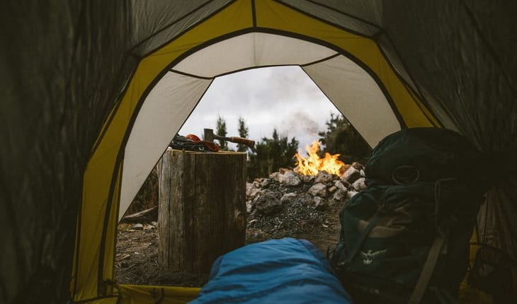 Person in a sleeping bag in tent looking outside