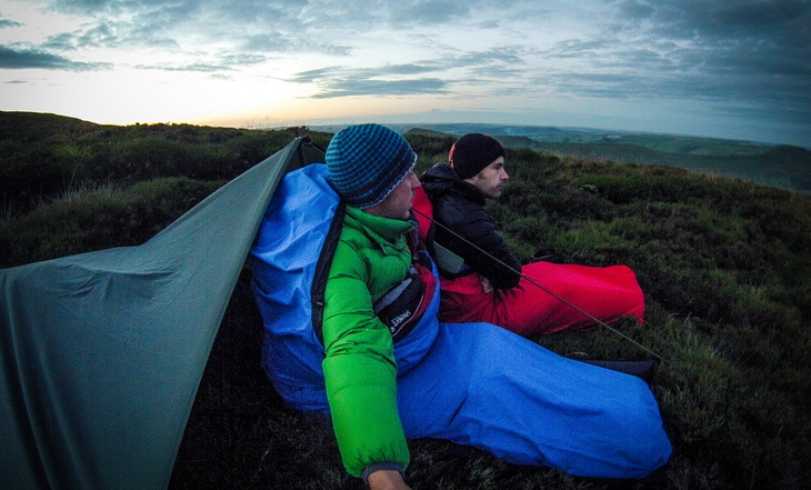Two mens sitting in sleeping bags at down
