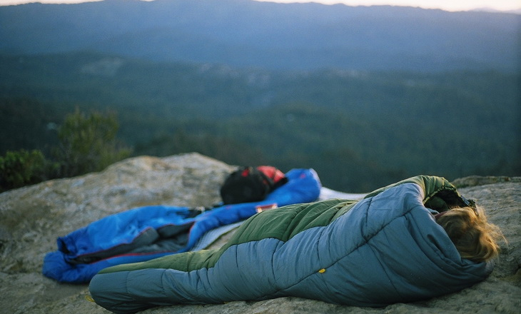 Person in a sleeping bag on top of the mountains