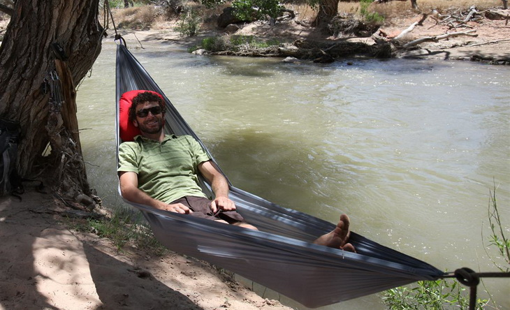 A man in Grand Trunk Nano 7 Hammock near a river
