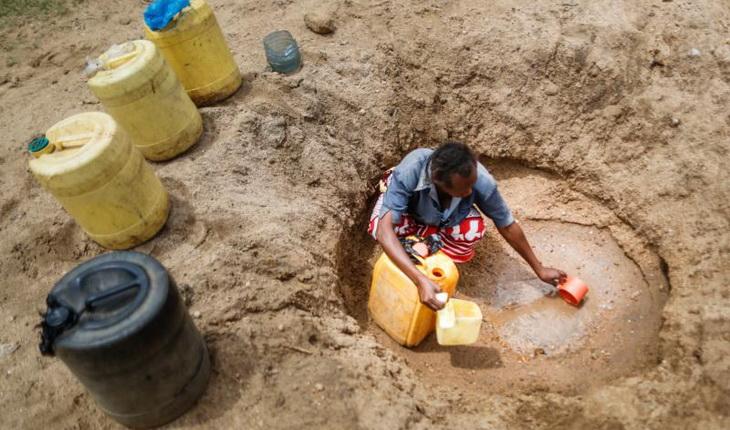 Woman Burrowing for Water in desert