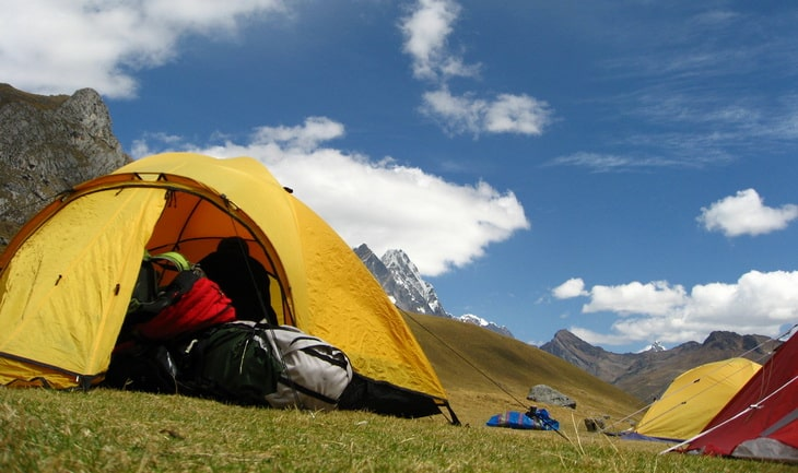 three tents in the picture and moutains in the background