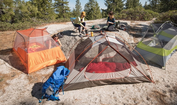 Three womans and three tents in the forest
