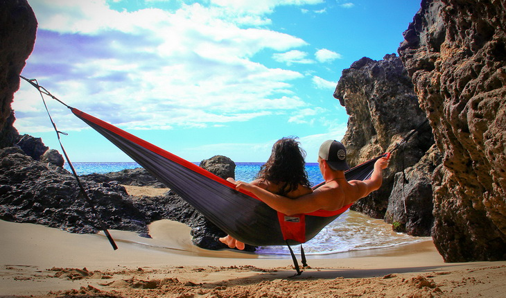 A couple relaxing in a ENO Eagles Nest Outfitters - DoubleNest Hammock and watching the Ocean