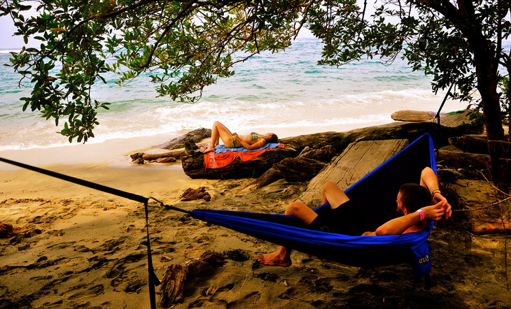 A man sitting in a Woman relaxing in a ENO Eagles Nest Outfitters - DoubleNest Hammock and watching the Ocean