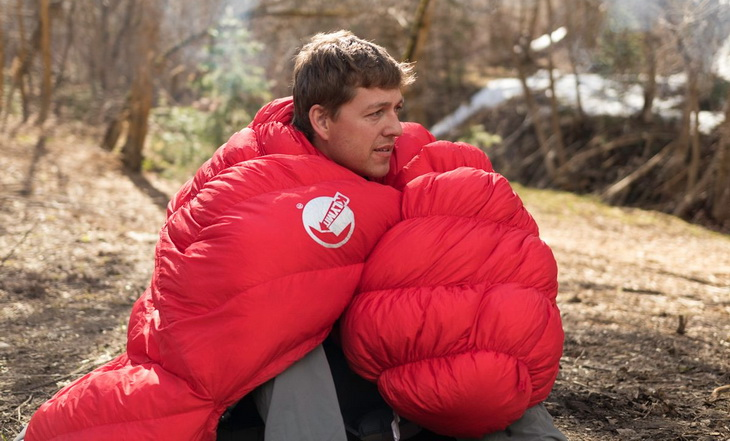 A man with Klymit KSB 20 Sleeping Bag on his shoulders