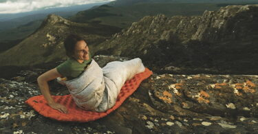 A woman sitting on Sea to Summit Ultralight Mat on top of the mountains