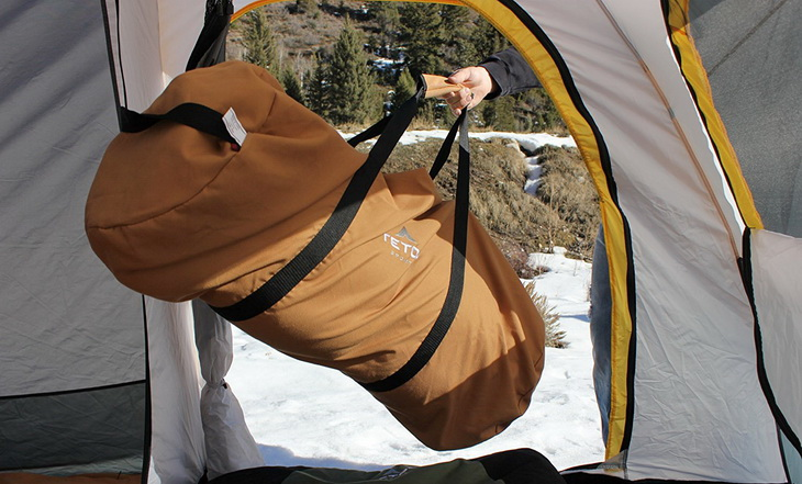 A person holding a Teton Sports Deer Hunter sleeping bag in a tent