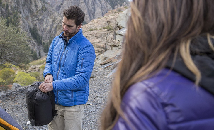 A man holding a TETON Sports Altos Sleeping Bag in a sack and his girlfriend next to him