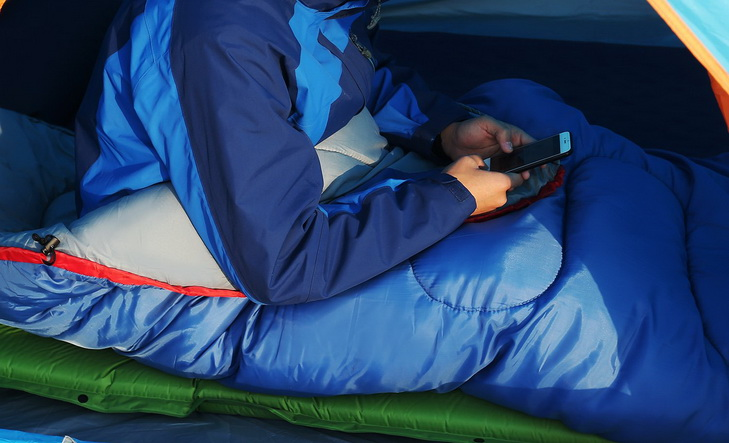 Man in a sleeping bag checking the phone