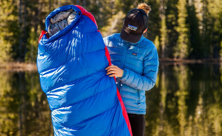 Woman holding an Outdoor Vitals Sleeping Bag