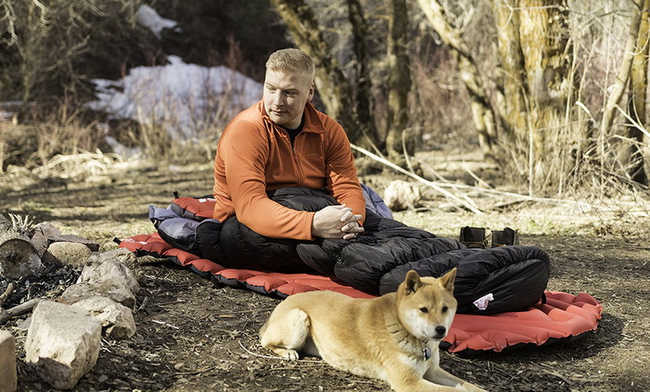 Man in Klymit KSB 20 Sleeping Bag and a dog next to him