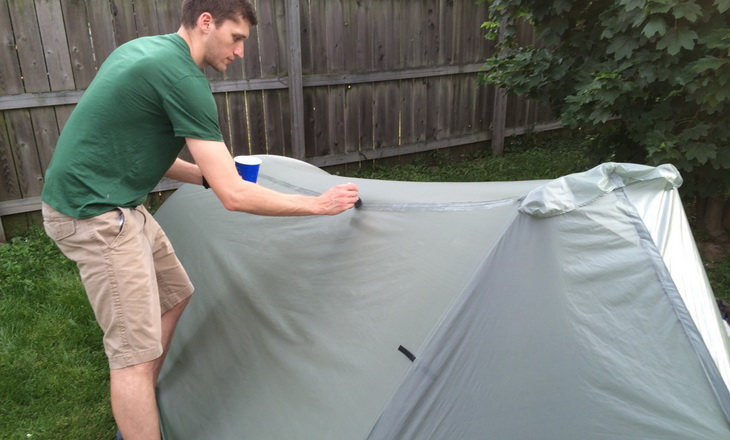 A man seam sealing his tent