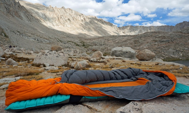 A sleeping bag and a mountain landscape in the background