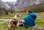 Woman in sleeping bag sitting on the grass and looking at her dog