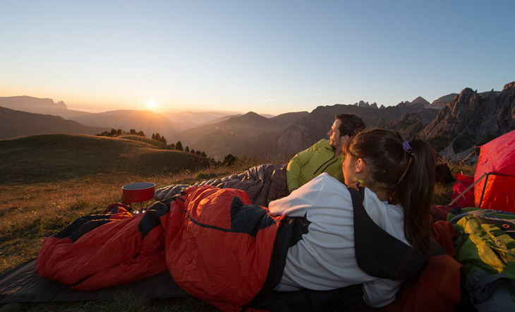 Two people laying in sleeping bags watching the sunrise