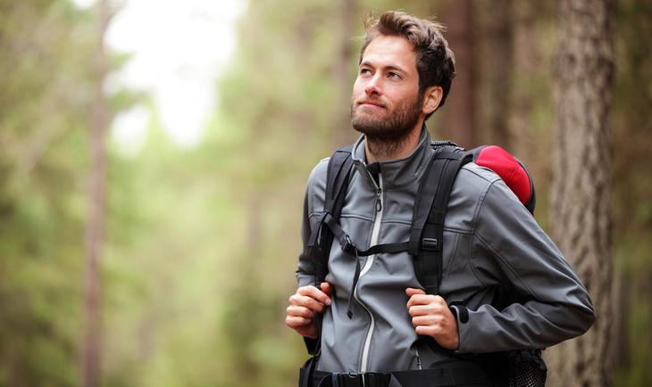 man hiking in forest wearing a fleece jacket
