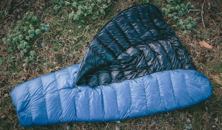 Blue sleeping bag on the ground