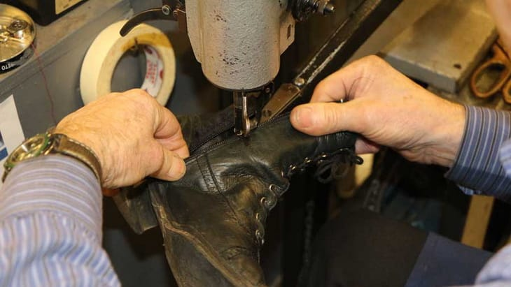 Brian stitching in a zip in a boot