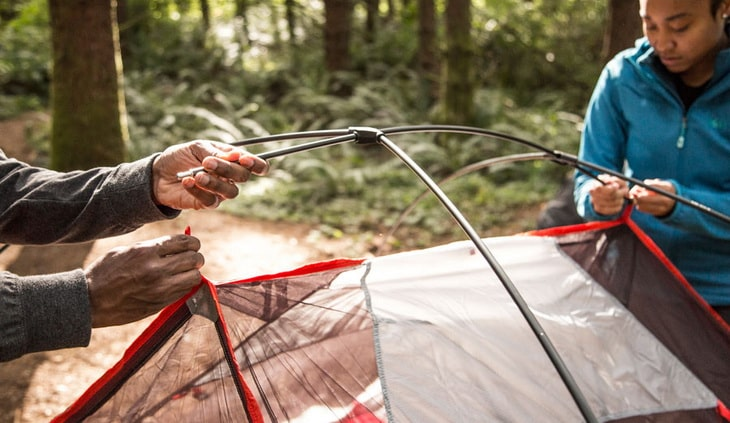 Two persons embeding tent poles