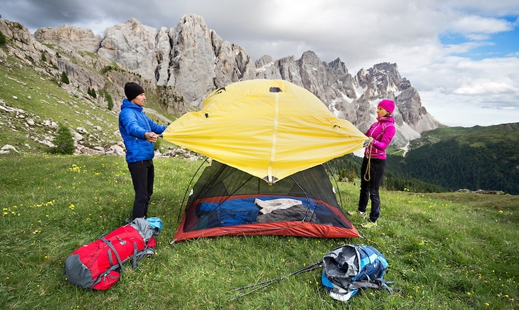 Couple setting up a tent and putting on the rainfly