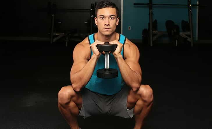 A Man Practicing Dumbbell Goblet Squat Exercise