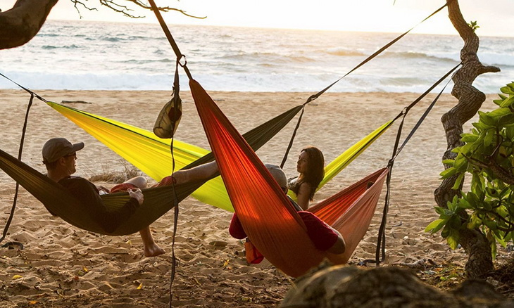 Adults sitting in Grand Trunk Hammocks on the beach