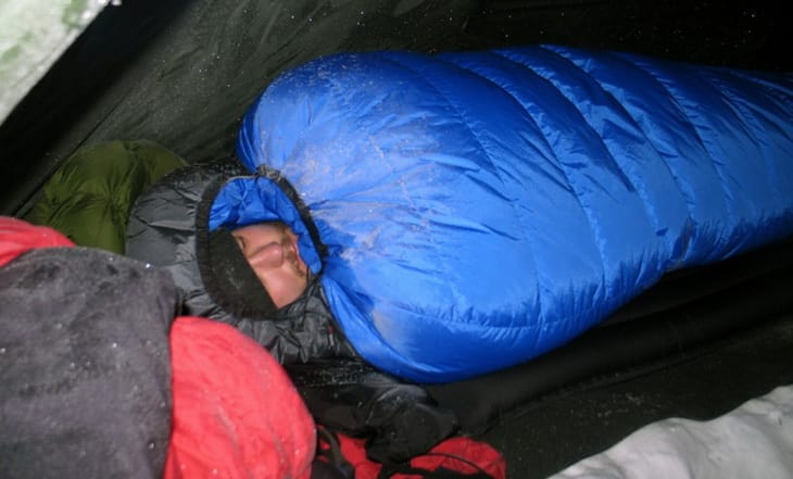 61b0ea179e66 Man sleeping in Close up of Western Mountaineering Puma Gore WS Sleeping Bag