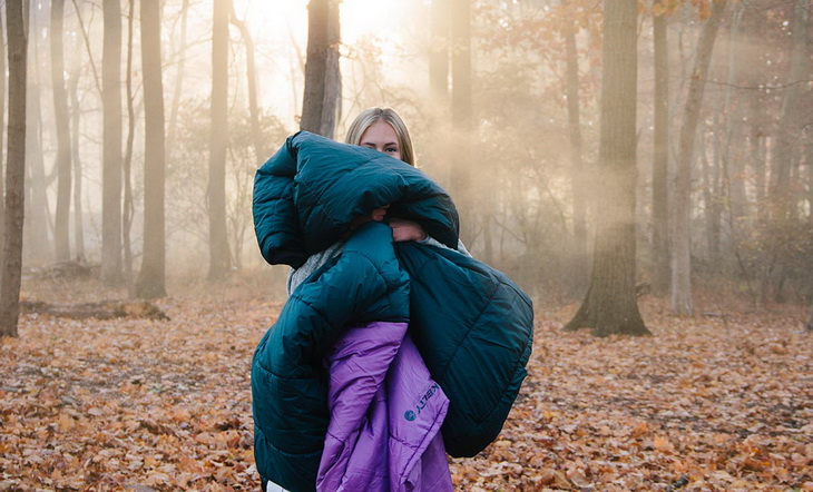 A woman in the forest holding Kelty sleeping bag