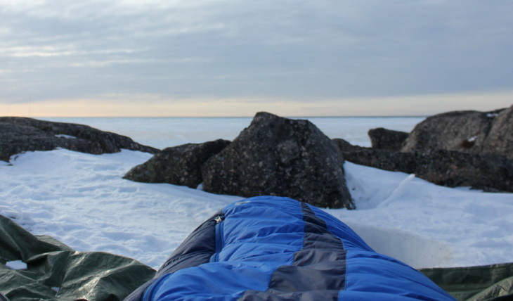 Image of a person sitting in a sleeping bag outside in the winter time