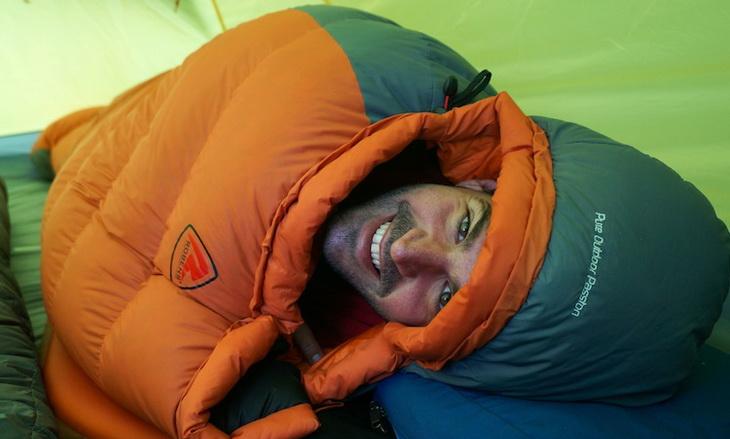 Man in a sleeping bag smiling at the camera