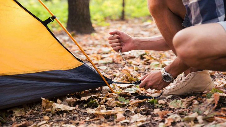 Man in plaid shirt and sneakers crouches on leaves to push tent peg into ground