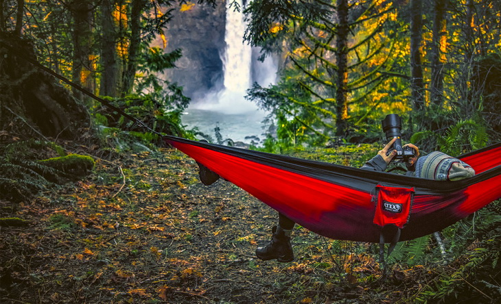 Man looking at his camera in Eagles Nest Double Hammock
